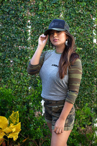 Woman wearing Youth Baseball tee with heather grey body and camo print sleeves screen printed with black Aloha Shapes logo on left chest