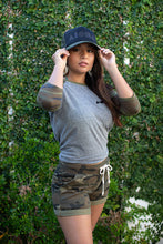Woman wearing Womens French Terry camo print shorts with white drawstring screen printed with black Aloha Shapes ® logo