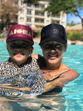 Mother and daughter in a pool both wearing Aloha Shapes® logo trucker hats