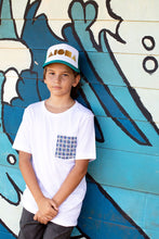 Young man wearing a Basketweave Aloha Shapes pocket tee in front of a graffiti wall