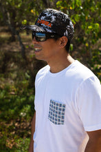 Smiling man on beach wearing white color unisex pocket tee with basketweave Aloha Shapes® design.