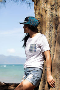 Smiling woman leaning on tree at beach wearing white color unisex pocket tee with basketweave Aloha Shapes® design.