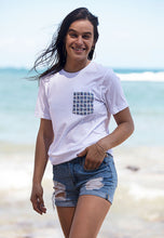 Smiling woman on beach wearing white color unisex pocket tee with basketweave Aloha Shapes® design.
