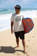 Man on beach holding bodyboard wearing Maui Jim sunglasses and Unisex Tee with basketweave Aloha Shapes print logo
