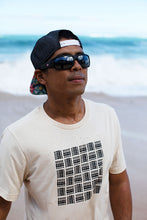 Man on beach wearing shades and backwards hat and Unisex Tee with basketweave Aloha Shapes print logo