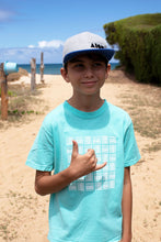 Young boy on beach throwing shaka in Paia Maui wearing our Basketweave Aloha Shapes logo youth tee
