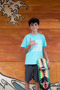 Young man holding a skateboard and throwing a shaka wearing Aloha Shapes Basketweave youth tee