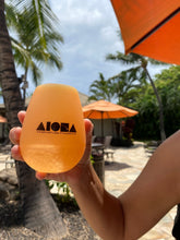 Person at a pool in tropical Hawaii holding an orange Aloha Shapes ® logo silicone beach cup