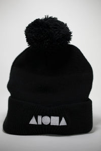Adult beanie with poof top in black. Embroidered with white ALOHA Shapes ® logo