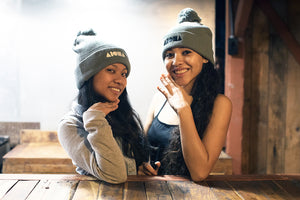 Two cute girls wearing ALOHA Shapes ® logo beanie caps in a coffee shop