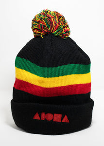 black knit cuffed beanie with red, yellow, green stripe around head and multi-color pompom on top. Embroidered with red Aloha Shapes logo.