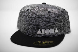 Adult flat brim snapback hat. Black canvas flat brim. Black/white squiggly pattern fabric on panels. White embroidered Aloha Shapes® logo on front.