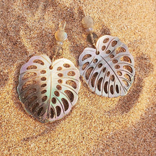 Monstera leaf shaped earrings carved from abalone shell with labradorite gemstones. Handmade in Maui, Hawaii. Featured placed on beach sand