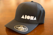 Black ALOHA Shapes ® logo Flexfit hat sitting on a wooden desk