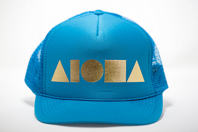 Adult foam trucker hat. Turquoise brim, front foam panel and mesh back panels. Foil printed with gold ALOHA Shapes ® logo