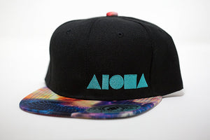 Youth flat brim snapback hat. Satin space/cosmic fabric on brim. Black panels embroidered with white ALOHA Shapes ® logo