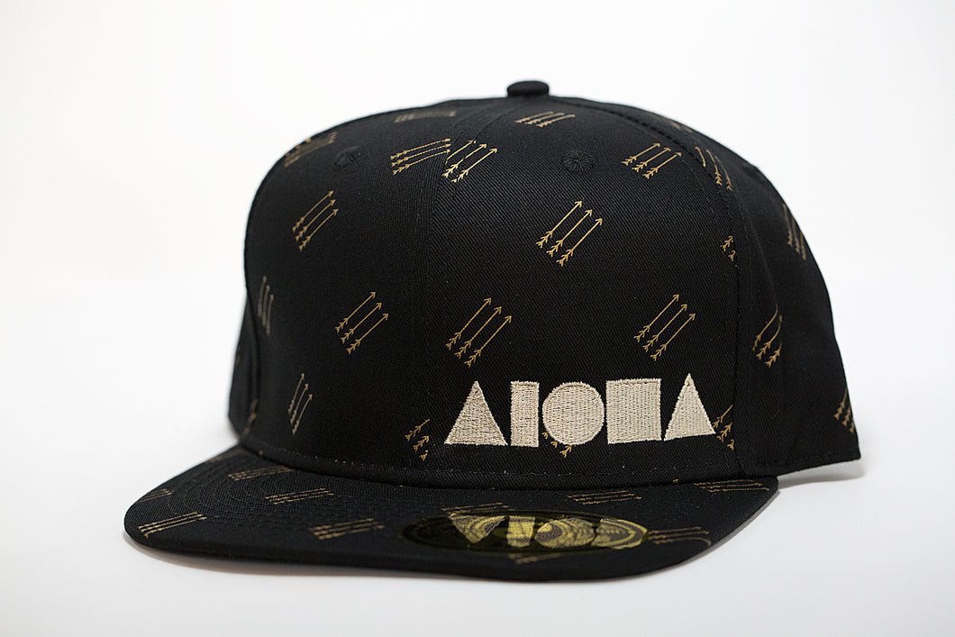 Adult flat brim snapback hat. Black fabric with gold arrows printed all over hat. Embroidered with cream color ALOHA Shapes ® logo