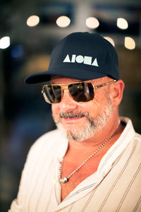 Older gentleman wearing an ALOHA Shapes ® logo Flexfit hat and dark sunglasses