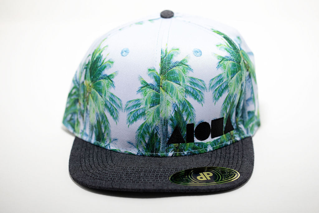 Light blue fabric with coconut palms on adult flat brim snapback hat embroidered with black Aloha Shapes ® logo