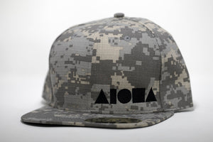 Adult flat brim snapback hat. Greyscale digital camo print fabric with black embroidered Aloha Shapes® logo.
