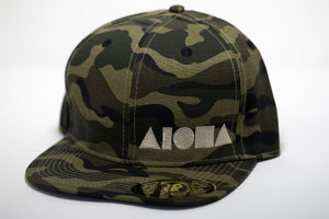 Adult flat brim snapback hat.  Military green/brown camo fabric all over hat. Embroidered with cream color ALOHA Shapes ® logo