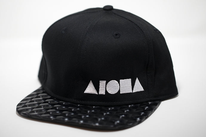 Adult flat brim snapback hat. Black hologram square material on brim. Black canvas fabric panels. Embroidered with white ALOHA Shapes ® logo