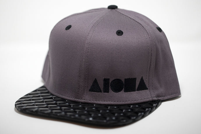 Adult flat brim snapback hat. Black hologram square material on brim. Grey canvas panels. Embroidered with black ALOHA Shapes ® logo