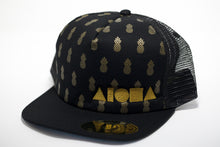 Adult flat brim snapback hat. Black brim. Black fabric front panels printed with gold pineapple symbols. Black mesh back panels. Embroidered with gold ALOHA Shapes ® logo