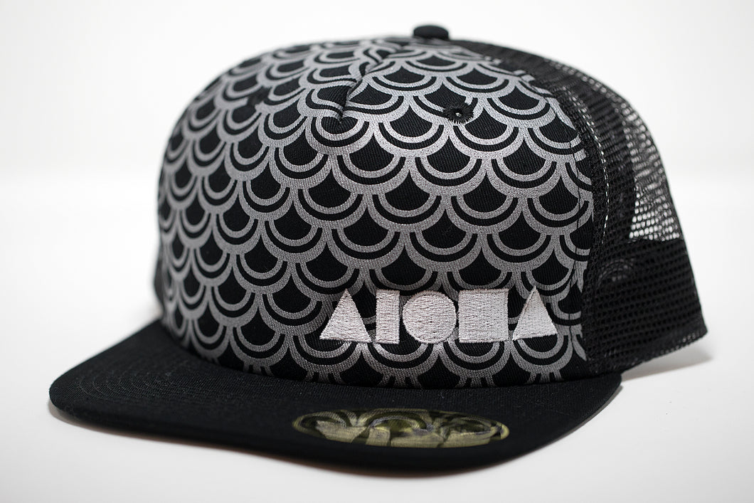 Adult flat brim snapback hat. Black brim. Black foam front  panel printed with silver fish scale pattern. Black mesh back panels. Embroidered with white ALOHA Shapes ® logo