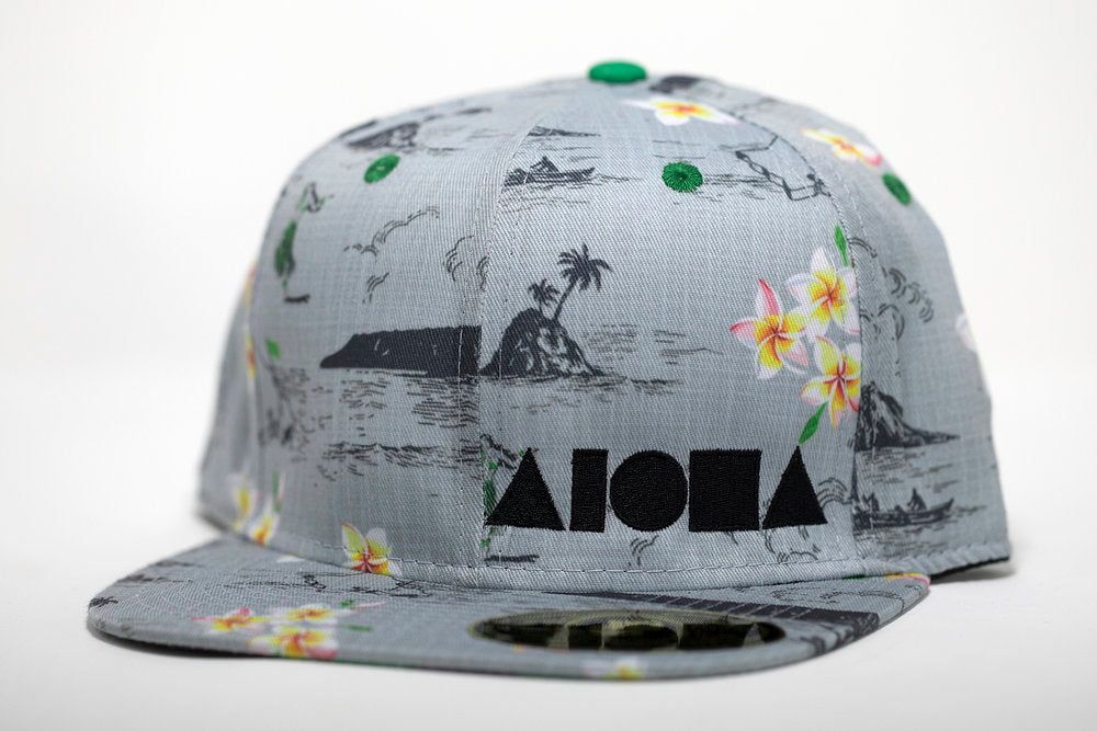 Adult flat brim snapback hat. Light blue fabric printed with Diamondhead, hula girls and golf course greens all over hat. Embroidered with black ALOHA Shapes ® logo