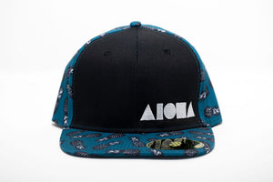 Adult flat brim snapback with black front panels and blue pineapple printed fabric on back