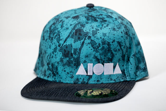 Adult flat brim snapback hat. Grey denim brim. Blue fabric with a paint splatter-like print. Embroidered with white ALOHA Shapes ® logo