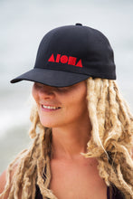 Young blond dreadlocked girl wearing an ALOHA Shapes ® logo Flexfit hat on the beach