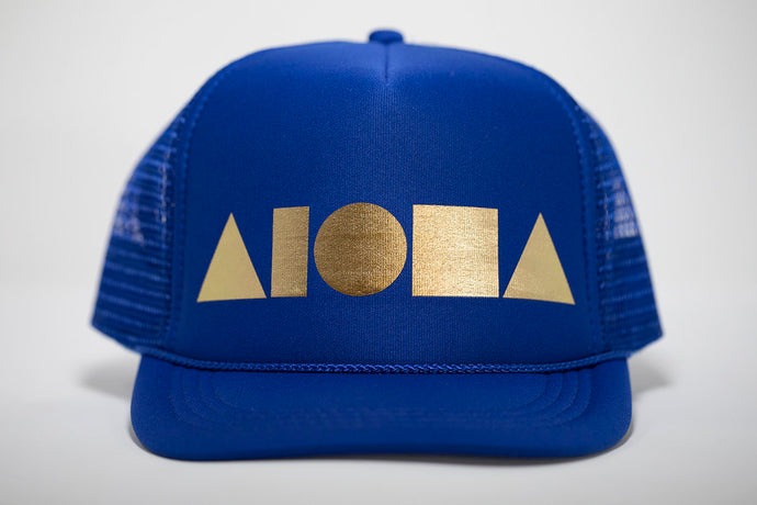 Youth foam trucker hat. Blue bill. Blue foam front panels with gold foil print Aloha Shapes® logo. Blue mesh back panels.
