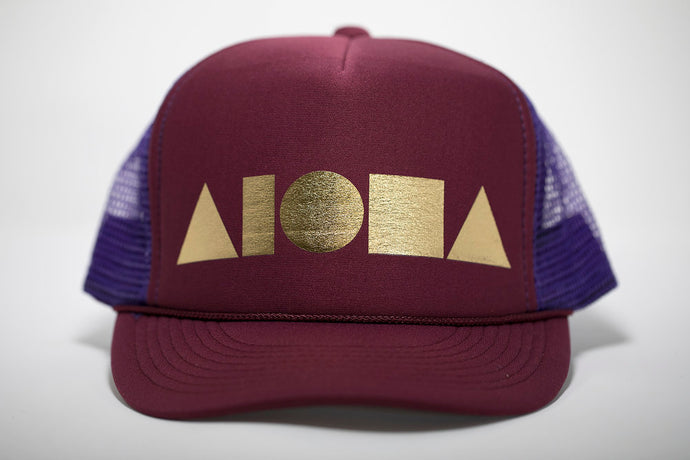 Adult foam trucker hat. Maroon brim and front foam panel foil printed with gold ALOHA Shapes ® logo. Purple mesh back panels.