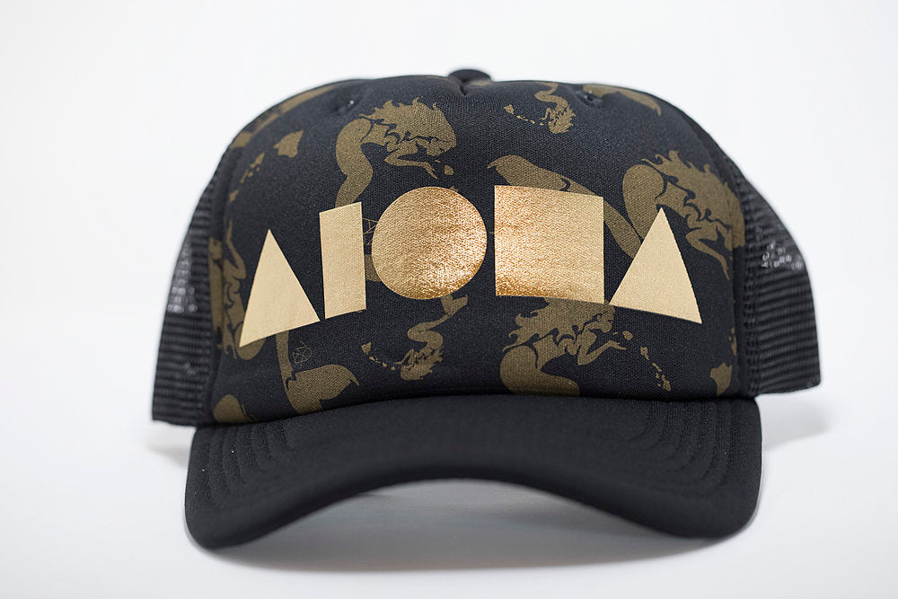 Adult foam trucker hat. Black curved brim. Black foam front panel printed with gold mermaids blowing a kiss of the Hawaiian island chain. Black mesh black panels. Foil printed with gold ALOHA Shapes ® logo