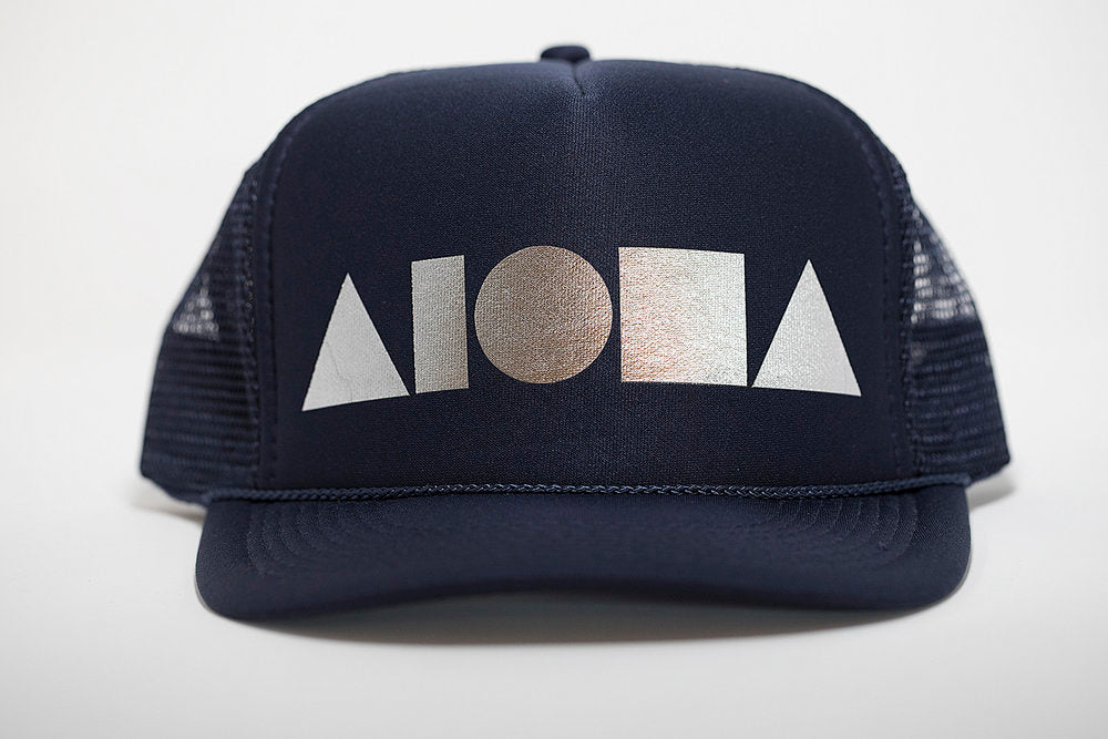 Adult foam trucker hat. Navy brim and front foam panel foil printed with silver ALOHA Shapes ® logo. Navy back mesh panels.