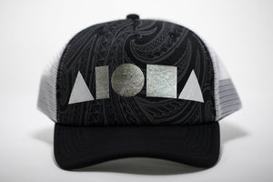 Adult foam trucker hat. Black curved brim. Black/grey tribal pattern on front panel foil printed with silver ALOHA Shapes ® logo. White mesh back panels.