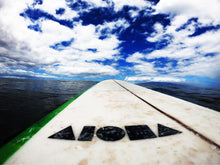 Surfboard with an all black ALOHA Shapes ® logo decal sticker in the ocean.