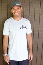 Man smiling wearing silver Giving tree design t-shirt showing Aloha in cursive on left chest front