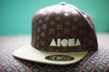 """Hawaiian quilt"" ALOHA Shapes ® logo snapback hat laid on a brown fabric background."