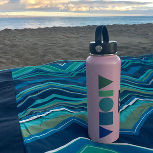 Hydroflask water bottle with a Blue Dream Aloha Shapes logo sticker on a beach blanket with Hawaii sunset in background