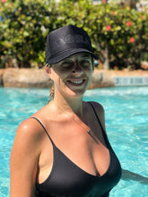Happy woman in a pool wearing an Aloha Shapes ® black/black sparkles trucker hat