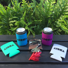 Assortment of Aloha Shapes ® logo koozies spread out in front of tropical foliage