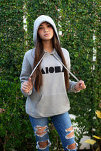 Young woman wearing Heather stone colored unisex pullover hoodie with black Aloha Shapes® logo hand-screenprinted on front chest and torn up jeans. Handmade in Maui Hawaii