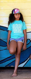 Young girl leaning against a wall in Paia, Maui wearing a Basketweave Aloha Shapes youth tshirt