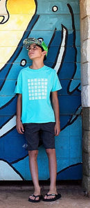Young boy standing against a graffiti backdrop wall in Paia Maui wearing our Basketweave Aloha Shapes logo youth tee