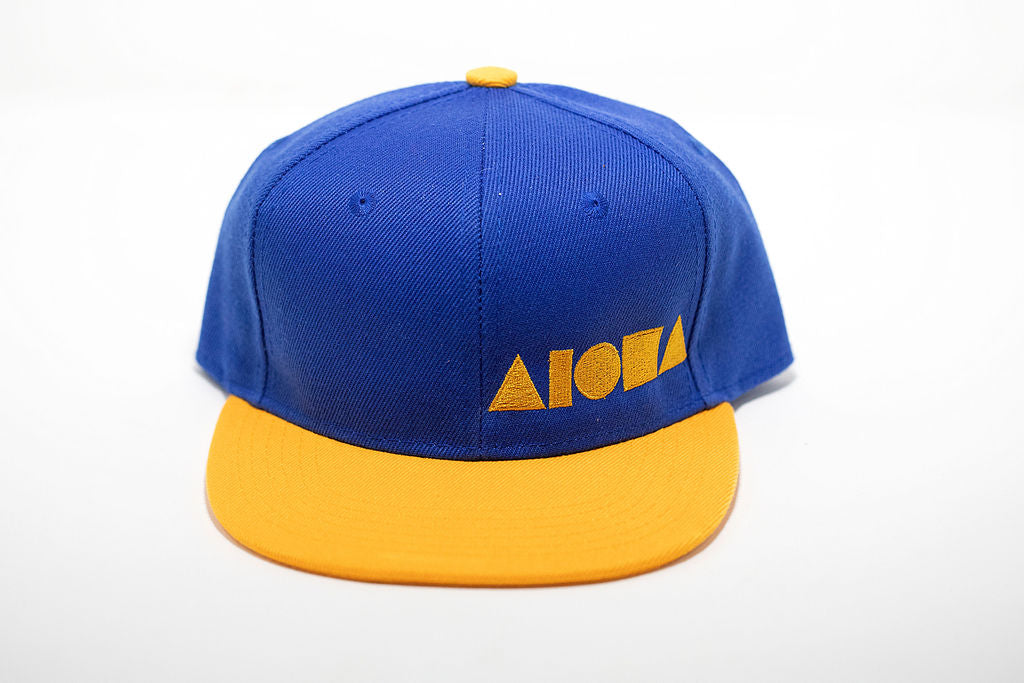 Blue and yellow youth flat brim snapback hat embroidered with yellow Aloha Shapes ® logo
