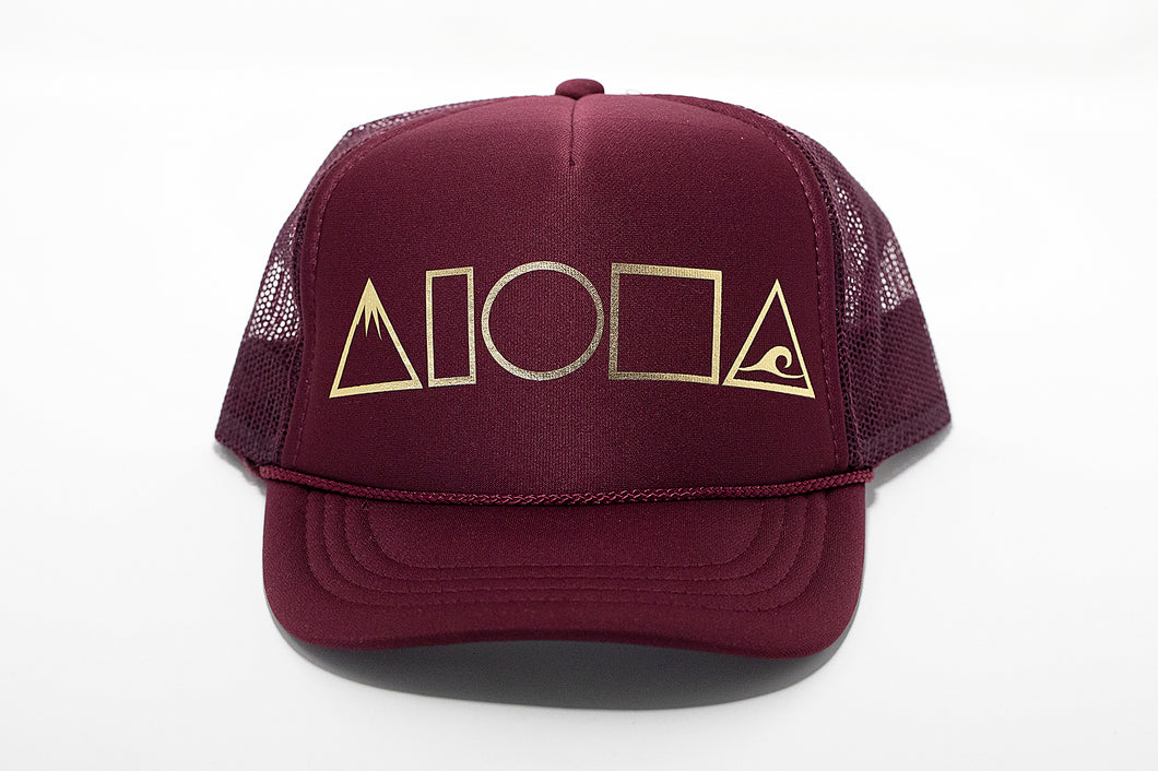 Maroon foam trucker hat printed with our new Mauka to Makai Aloha Shapes logo in metallic gold