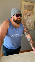 Person wearing Heather blue unisex triblend tank top printed on front chest with white Mauka to Makai Aloha Shapes logo leaning on countertop wearing beanie cap and sunglasses